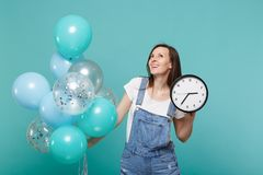 Dreamful young woman in denim clothes looking up, holding round clock and celebrating with colorful air balloons