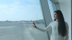 Dreamily meisjestribune dichtbij het venster en blikken op de baan met vliegtuigen stock video