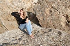 Dreamily ung kvinna som kopplar av på stora stenar Royaltyfri Foto