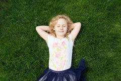 Dreaming adorable girl lying on grass, top view Royalty Free Stock Photo