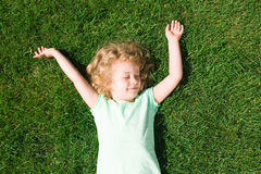 Dreaming adorable little girl lying on grass Royalty Free Stock Photos