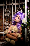 Dreaming anime girl in purple wig with toy Royalty Free Stock Photos