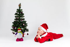 Dreaming baby boy dressed as Santa Claus lying next to Christmas Stock Images