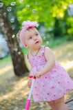 Dreaming baby girl. In a pink dress with a pink ribbon walking in the park stock photography