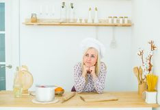 Dreaming beautiful blonde girl is in the kitchen stock photo