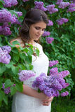 Dreaming beautiful bride posing near blooming lilac tree Stock Image