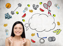 Dreaming beautiful brunette lady is thinking about her choice of sport activity. Colourful sport icons are drawn on the concrete w. All. A concept of a healthy Royalty Free Stock Photo
