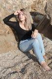 Dreaming beautiful girl sitting  on big stones. Royalty Free Stock Photo