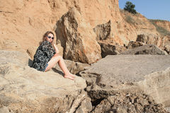 Dreaming beautiful girl sitting  on big stones. Royalty Free Stock Photography