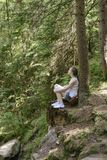 Dreaming beautiful girl sitting on a stone surrounded by coniferous forest on a sunny day. Vertical frame.  stock photography
