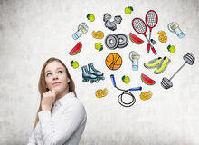 Dreaming beautiful lady is thinking about her choice of sport activity. Colourful sport icons are drawn on the concrete wall. A co Royalty Free Stock Image