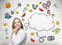 Dreaming beautiful lady is thinking about her choice of sport activity. Colourful sport icons are drawn on the concrete wall. A co Royalty Free Stock Photo