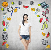 Dreaming beautiful lady is thinking about her choice of sport activity. Colourful sport icons are drawn on the concrete wall. A co Stock Photos