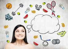 Dreaming beautiful lady is thinking about her choice of sport activity. Colourful sport icons are drawn on the concrete wall. A co. Ncept of a healthy lifestyle Royalty Free Stock Photos