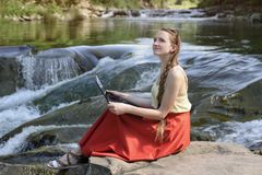 Dreaming beautiful long-haired girl in a red skirt sits with with a laptop on a stone against the backdrop of a cascade of a stock photo