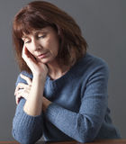 Dreaming beautiful 50s woman looking contemplative. Portrait of mature woman with brown hair and blue winter sweater thinking,face resting on hand,looking sad Royalty Free Stock Photography