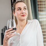 Dreaming beautiful young woman enjoying holding wine glass for degustation. Dreaming beautiful young woman enjoying holding a wine glass for degustation and royalty free stock photography