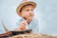 Dreaming boy with book lies on hay stack Royalty Free Stock Image