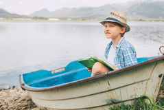 Dreaming boy with book sits in old boat on the mountain lake ban Royalty Free Stock Photography