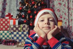 Dreaming boy in front of the christmas tree Stock Photo