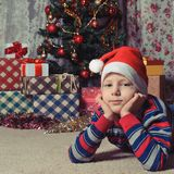Dreaming boy in front of the christmas tree Stock Images