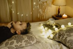 Dreaming boy lying in bed evening in dark against the background. Of lanterns Stock Photo