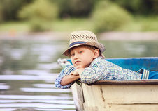 Dreaming boy lying in old boat on the river Stock Photography