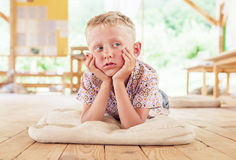 Dreaming boy lying on summer terrace Stock Photo