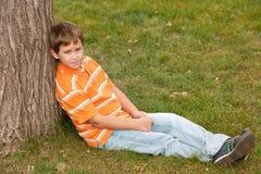 Dreaming boy near the tree Royalty Free Stock Photo
