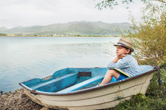 Dreaming boy in old boat at the lake coast Royalty Free Stock Images