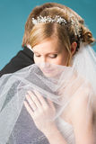 Dreaming bride. Beautiful bride dreaming something under veil and hugs her groom, she looks quite down stock photography