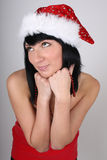 Dreaming brunette woman in santa hat Royalty Free Stock Image