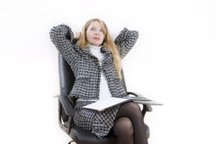 Dreaming about business. A woman sitting in a black chair and thinking Royalty Free Stock Photos