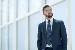 Dreaming businessman standing in a bright office. royalty free stock images