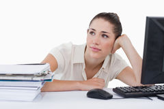 Dreaming businesswoman leaning on her desk Stock Photos