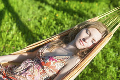 Dreaming Caucasian Blond Woman Resting in Hummock Outdoors. Stock Photos