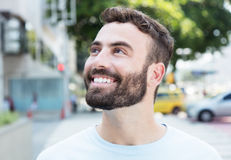 Dreaming caucasian man with beard outdoor in city. With streets and buildings in the background Royalty Free Stock Photos