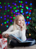 Dreaming child girl with book over bright back Royalty Free Stock Photos