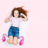 Dreaming child with headphones listening to music Stock Image