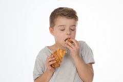 Dreaming child. Kid tastes a piece of croissant Stock Images