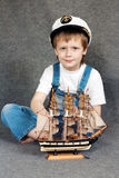 Dreaming child with the model ship. Royalty Free Stock Photography