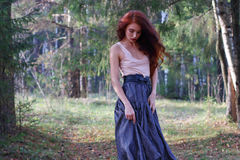 Dreaming cute girl in skirt walks on wind in forest Stock Photo