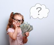 Dreaming cute kid girl in glasses looking on money and thinking. How can spend its with illustration bubble and question sign above on blue background stock photos