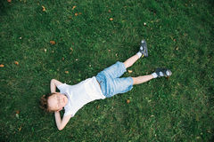 Dreaming cute kid lying on the green grass among fallen leaves Royalty Free Stock Photos