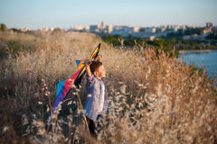 Dreaming cute little boy with colorful kite on the field with sea and town on background. Dreaming cute little boy with eyes closed with colorful kite on the Royalty Free Stock Photos