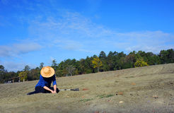 Dreaming of Diamonds. Woman, wearing a straw hat, sits in the dirt field at Crater of Diamonds State Park in Murfreesboro, Arkansas. She is digging for diamonds stock photography