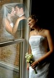 Dreaming on a Dreamy Day. Bride leans against window frame and dreams of the moment they say I do and kiss.  she has on a strapless gown and is hold a bouquet of Royalty Free Stock Photo