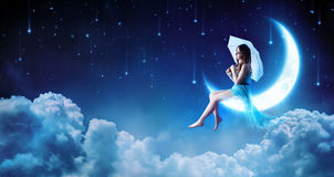 Dreaming In The Fantasy Night. Fashion Girl Sitting On Moon Royalty Free Stock Photos
