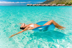 Dreaming float. Beautiful woman floating in turquoise waters near tropical resort Stock Photos