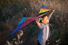 Dreaming about flying little boy holding kite above head. Standing on yellow field Royalty Free Stock Photography